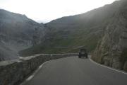 Klikatící se silnice zaříznutá v prudkém svahu hory Dreisprachenspitze - uprostřed nahoře Passo Stelvio
